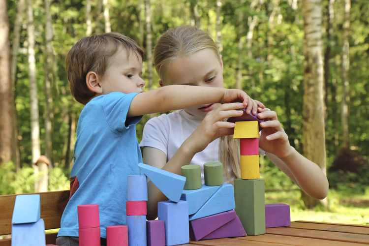 Cute siblings playing with toy blocks outdoors