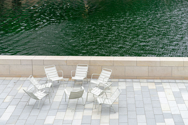High angle view of empty chairs by river