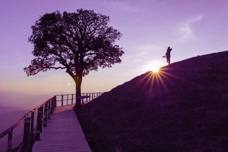 Silhouette Couple On Hill Against Sky During Sunset