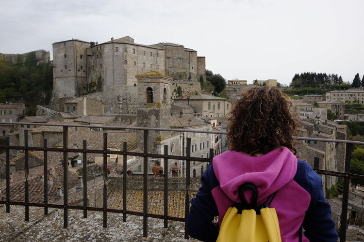 tourist admires the town of Sorano in Tuscany Architecture Built Structure Building Exterior Real People One Person Sky Rear View Standing Lifestyles Building Day Women Leisure Activity Hairstyle History Waist Up Nature Adult The Past Outdoors Warm Clothing From Behind