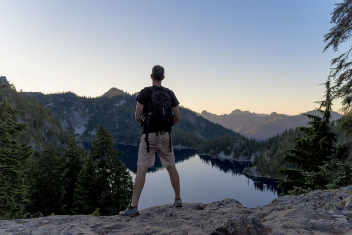 Rear view of a male hiker standing on a vista overlooking an alpine lake at dusk. Adventure Backpack Backpacking Beauty In Nature Clear Sky Day Full Length Hiking Landscape Leisure Activity Lifestyles Men Mountain Nature One Person Outdoors People Real People Rear View Rear View Scenics Sky Standing Tree Walking Lost In The Landscape