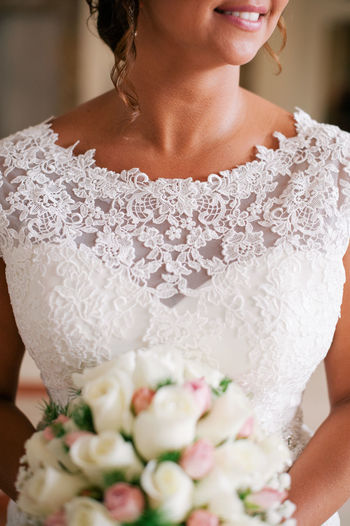 Midsection of bride with bouquet during wedding ceremony