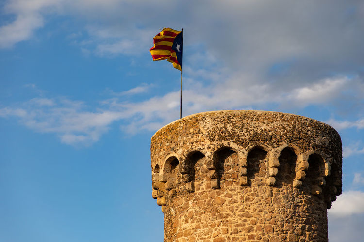Independentist flag waving on top of medieval tower cloudy sky Spain Flag Waving Yellow Estelada Spain Travel Patriotism Symbolism Worn Tower Bridge  Weathered Fabric Flagpole Europe Waving Flag Senyera Symbol Sign Travel Icons Wind Sky National Flag Star Stripes Outdoors Background Nation Catalonia Flag Banner Patriotic Blue National Buildings Independence Red Independent  Independency Revolution Republic Rebellion Cloudy Sky Cloudy Movement Medieval Tower Fortress Catalan Catalonia Catalan Flag
