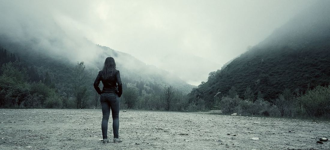 Rear view of woman standing against mountains during foggy weather