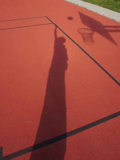 Shadow of man playing basketball on court