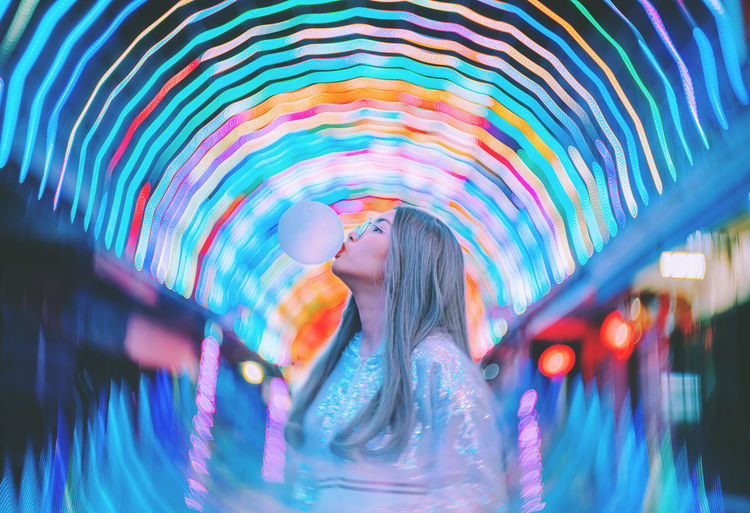 Woman blowing bubble gum while standing against illuminated lights