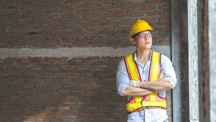 Low angle view of man working at construction site against brick wall