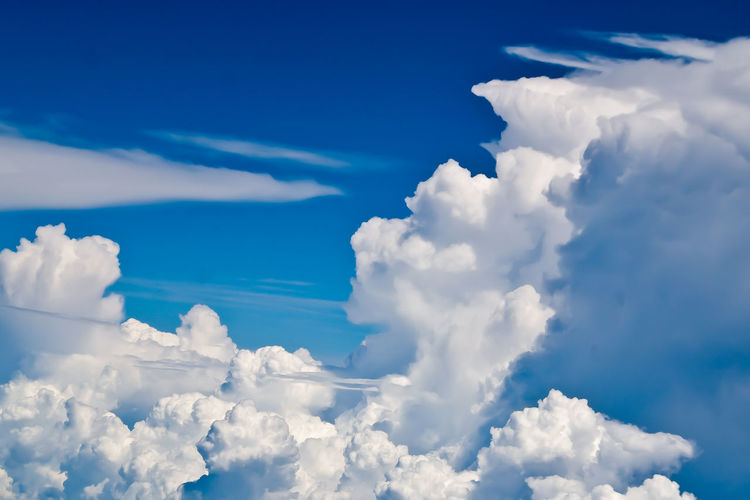 Beautiful fluffy white clouds against the blue sky as seen from an airplane. Aerial View Backgrounds Beauty In Nature Blue Cloud Cloud - Sky Cloudscape Cloudy Cumulus Cloud Day Idyllic Low Angle View Majestic Nature No People Outdoors Part Of Scenics Sky Sky Only Softness Tranquil Scene Tranquility Fine Art Photography White Color