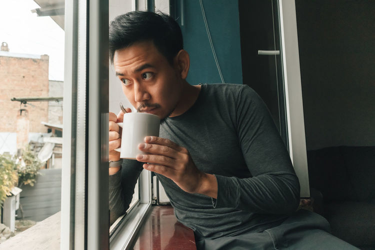 Man drinking coffee cup at home
