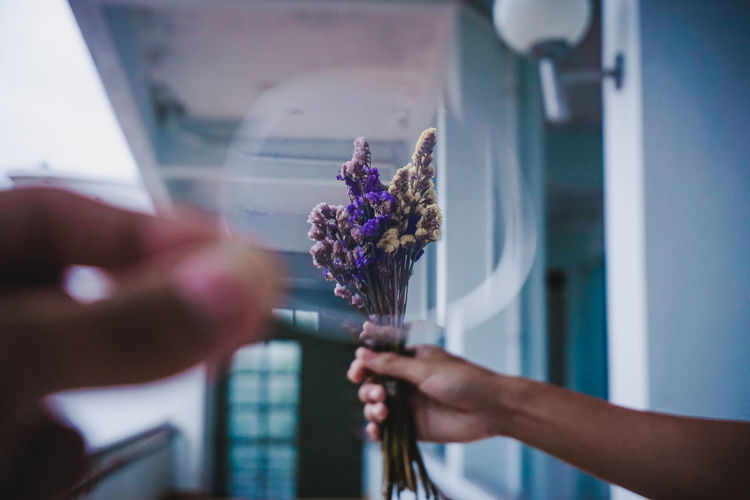 Cropped Hand Holding Glass Against Woman Holding Bouquet