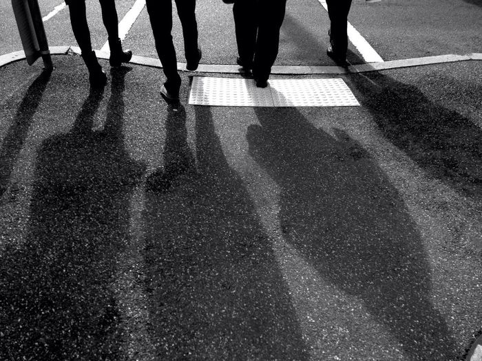 Low section view of four people crossing road
