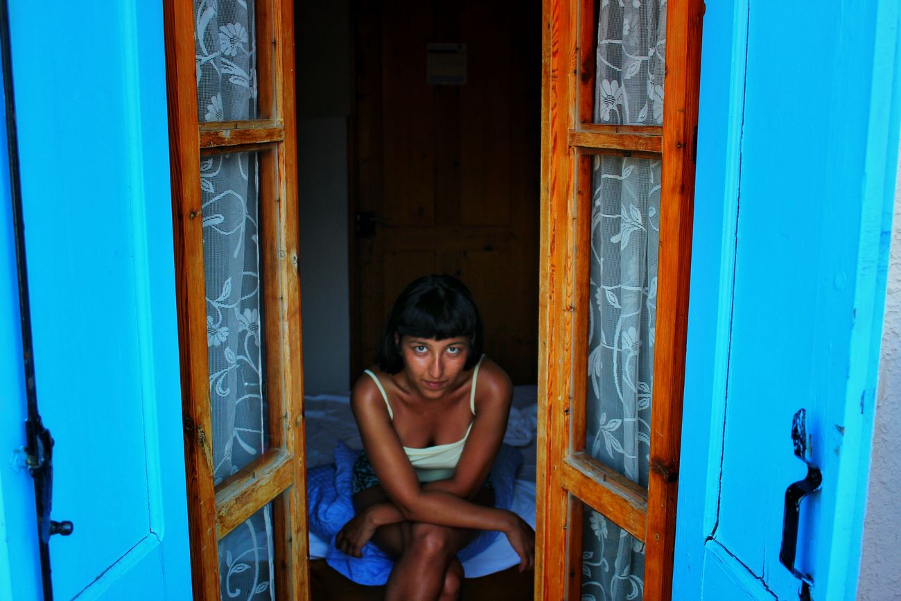 YOUNG WOMAN WITH CLOSED DOOR
