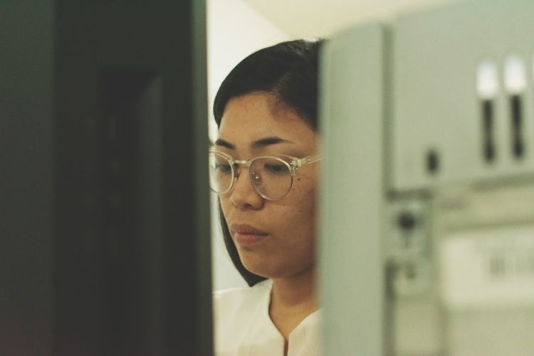 Close-up of serious young woman working in office