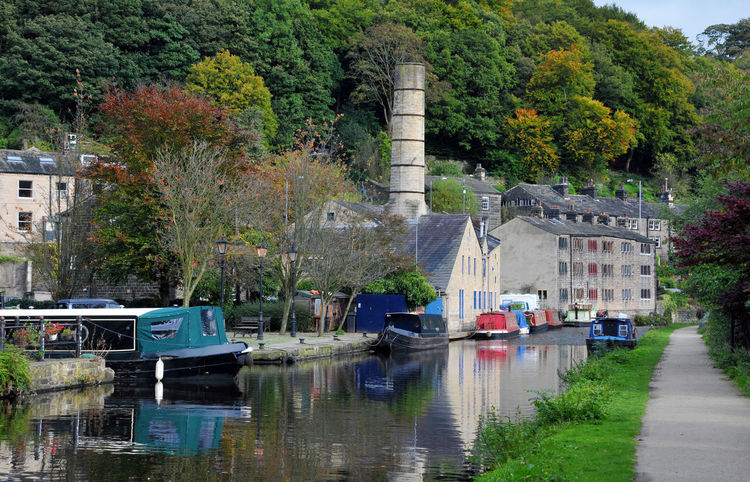 boats moored along the canal in hebden bridge uk Hebden Bridge Architecture Building Exterior Built Structure Canal Day Houseboat Moored Mooring Nature Nautical Vessel No People Outdoors Reflection Town Transportation Tree Water