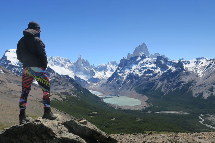 Rear view of person on snowcapped mountains against clear sky