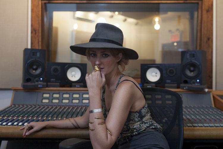 Portrait of woman wearing hat sitting in kitchen