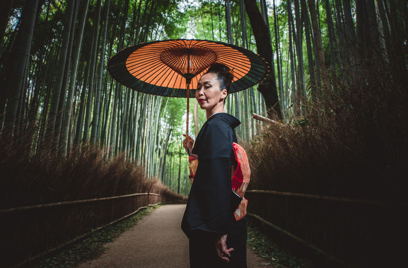 Side view of woman with umbrella standing amidst trees
