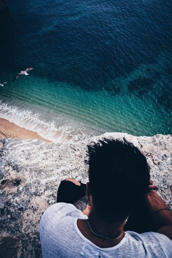 High angle view of man sitting on cliff by beach