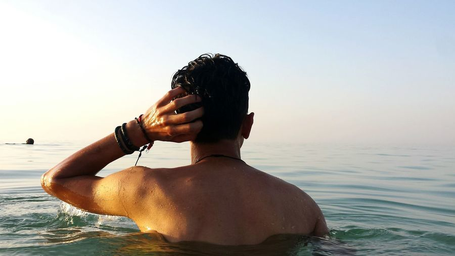Rear View Of Shirtless Man In Sea Against Sky