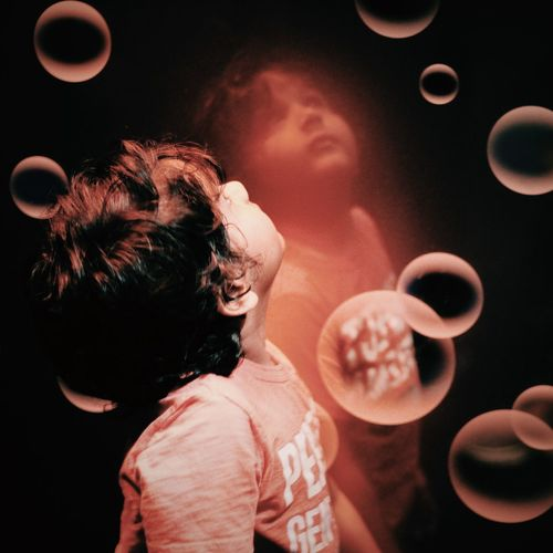Close-Up Of Boy Amidst Bubbles Against Mirror