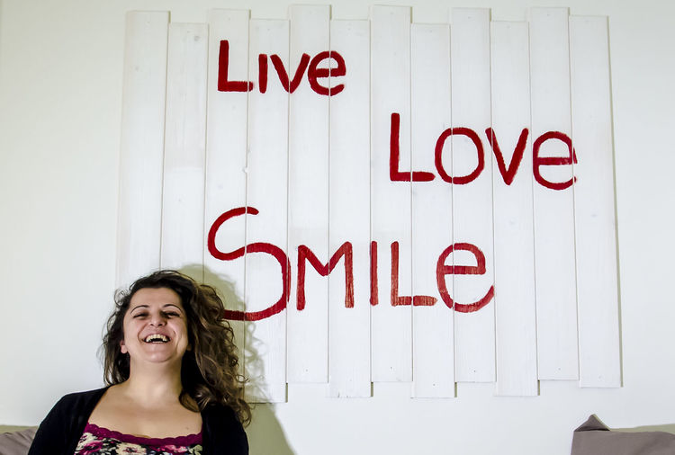 Smiling young woman standing against text