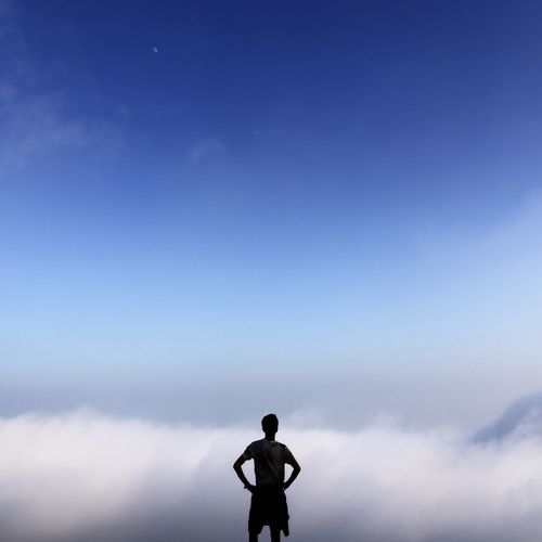 Rear view silhouette man standing against clouds with hands on hips