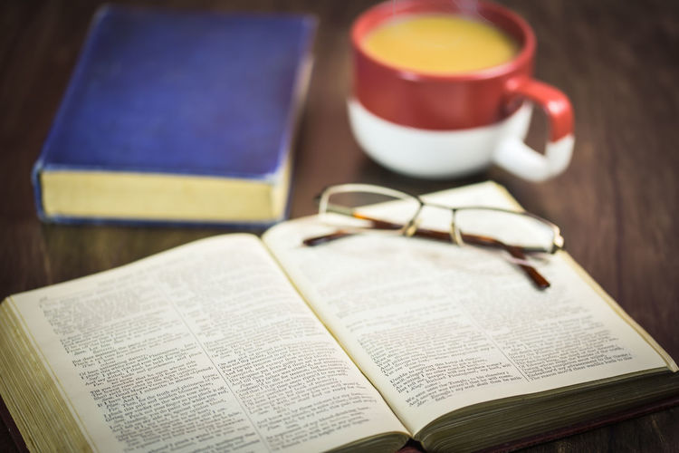 High angle view of books with eyeglasses and drink on table