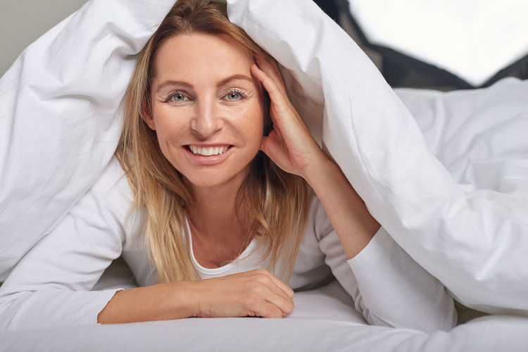 Beautiful middle-aged woman under sheets Beautiful Bed Home Looking At Camera Lying Pillow Woman Bedroom Best Ager Face Looking Lying Down Lying In Bed Middle-aged Portrait Sheets Smiling Woman Portrait