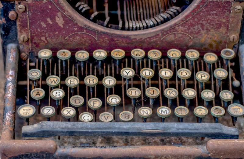 Beautiful old vintage typewriter with dusty key board and a bit of rust, for sale in an antique shop