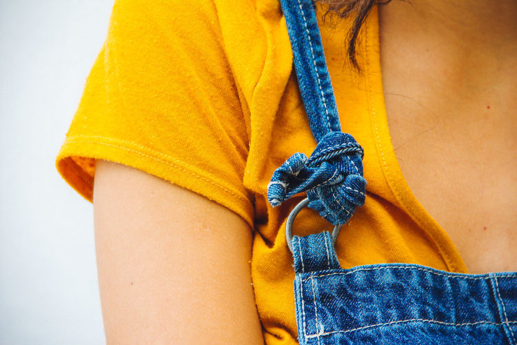 Cropped image of woman wearing bib overalls against wall