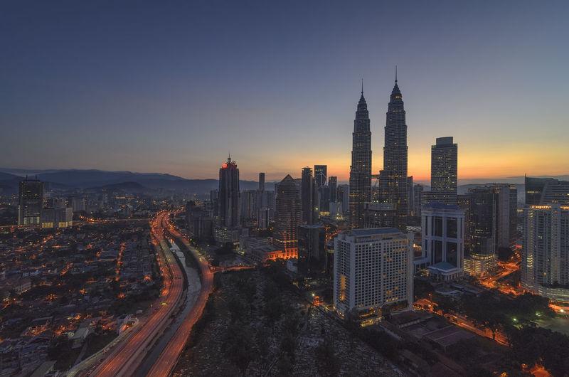 Petronas towers amidst buildings against sky during sunrise