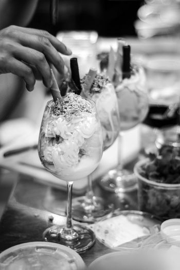 Close-up of hand holding ice cream on table in restaurant