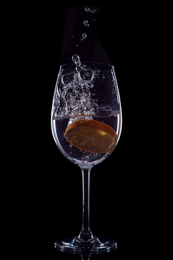 Close-up of wine glass against black background