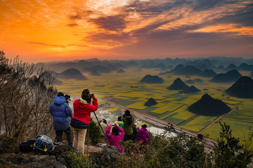 Tourist taking a picture for sunrise on the rock view from Luoping,Yunnan,China. Backpack Beauty In Nature Cloud - Sky Day Full Length Hiking Landscape Leisure Activity Lifestyles Men Mountain Mountain Range Nature Orange Color Outdoors Real People Scenics Sky Sunrise Sunset Togetherness Tranquil Scene Travel Destinations Vacations