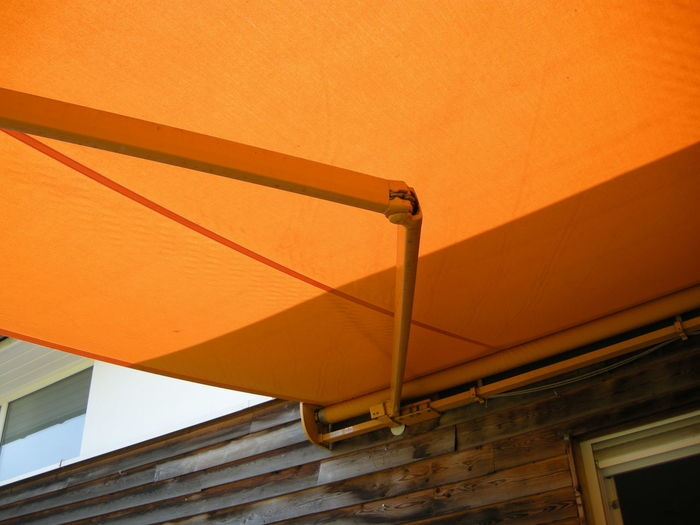 Low angle view of orange awning attached on wall