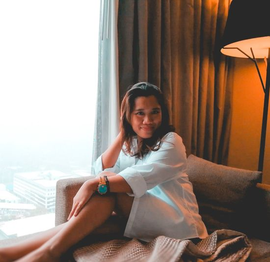 Portrait of woman sitting on sofa by window at hotel