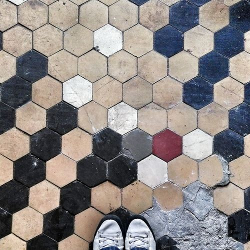 High angle view of pair of shoes on patterned footpath