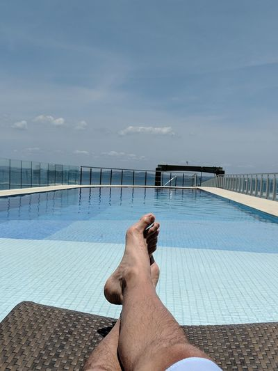 Low section of man in swimming pool against sky