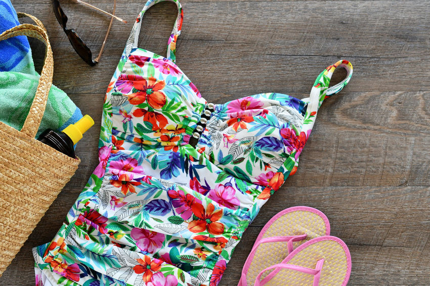 Summer flat lay of a woman's floral swimming suit, straw bag with a beach towel, suntan lotion, flipflops and sunglasses. Copy Space Essentials Pool Day  Summertime Travel Vacations Accessories Beach Beach Day Flat Lay Flatlay Floral Pattern High Angle View Multi Colored Pool Pool Bag Still Life Summer Swim Swimsuit Travel Destinations Vacation