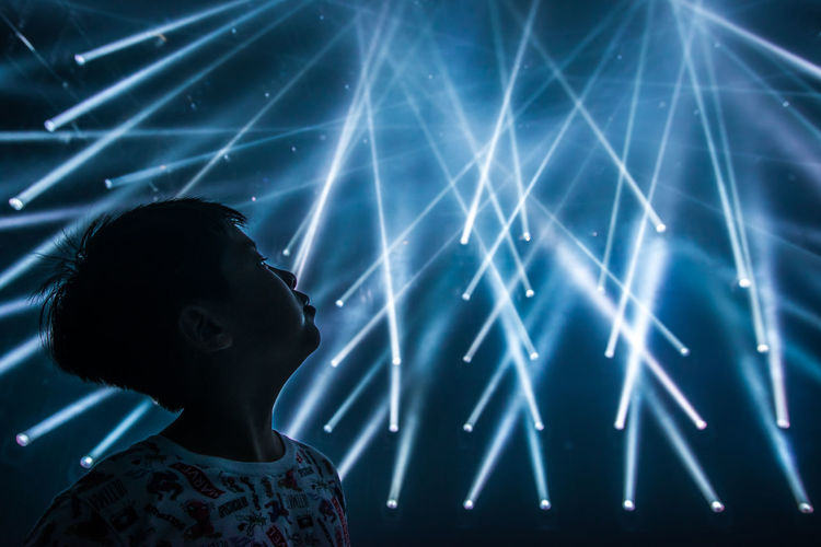 Boy looking away while standing against illuminated lights