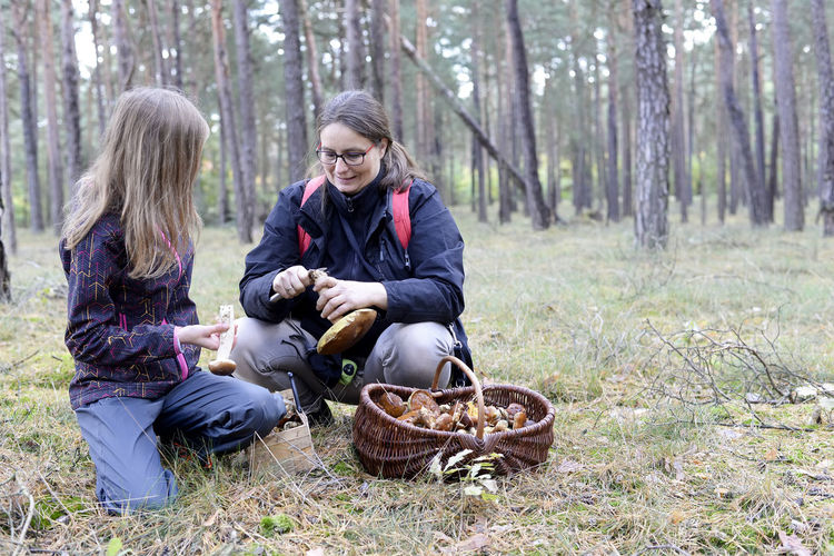 Woman with daughter collecting edible mushroom in basket at forest