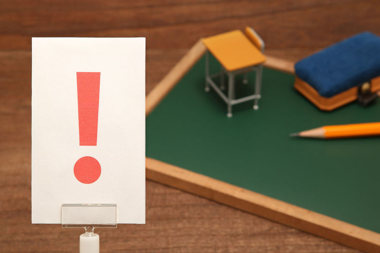 High angle view of exclamation point on paper with school supply toys on wooden table