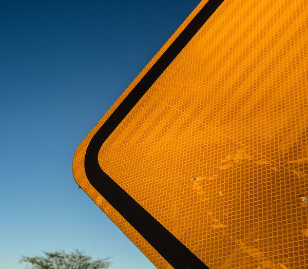 Partial view of a yellow traffic sign near a highway