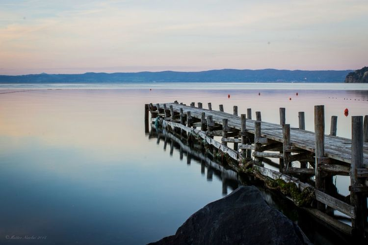 Wooden jetty in lake bolsena against sunset sky
