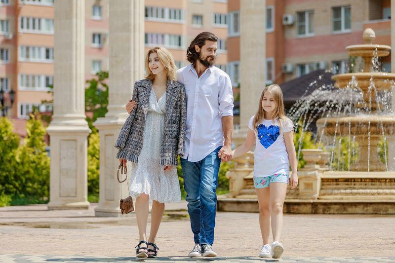 People walking on footpath against fountain