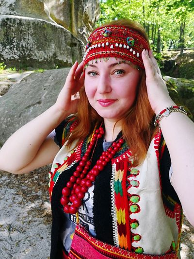 Portrait of beautiful woman wearing traditional clothing standing by rock in forest