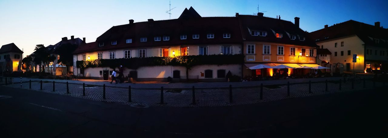 People on illuminated building against sky at night