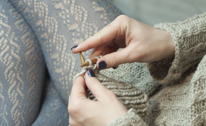 a young woman knits on the spokes and drinks coffee Knitting Lace Weaving Ajurno Knitting Needles Cozy Hands Home Knitted Sweater Openwork Text Background Woman Copy Space Craft Gray Hand Holding Human Hand Indoors  Keep Warm Lace Lace - Textile Openwork Textile Wool