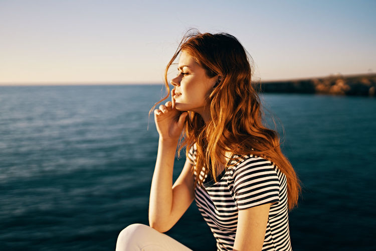 Beautiful young woman in sea against sky