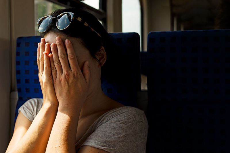 Woman covering face in train